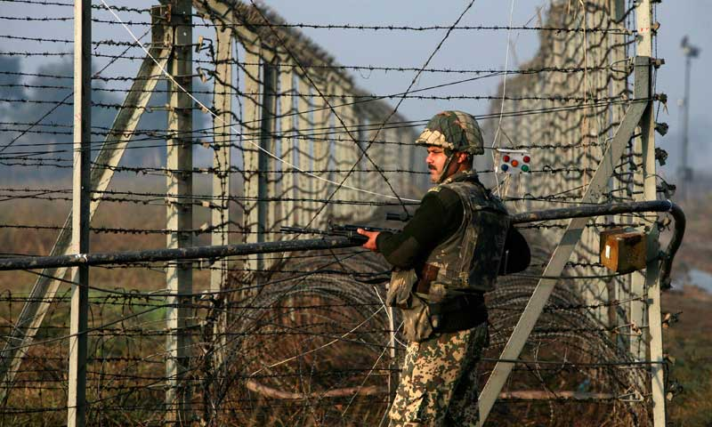 Indian BSF soldier patrols near fenced border with Pakistan in Suchetgarh